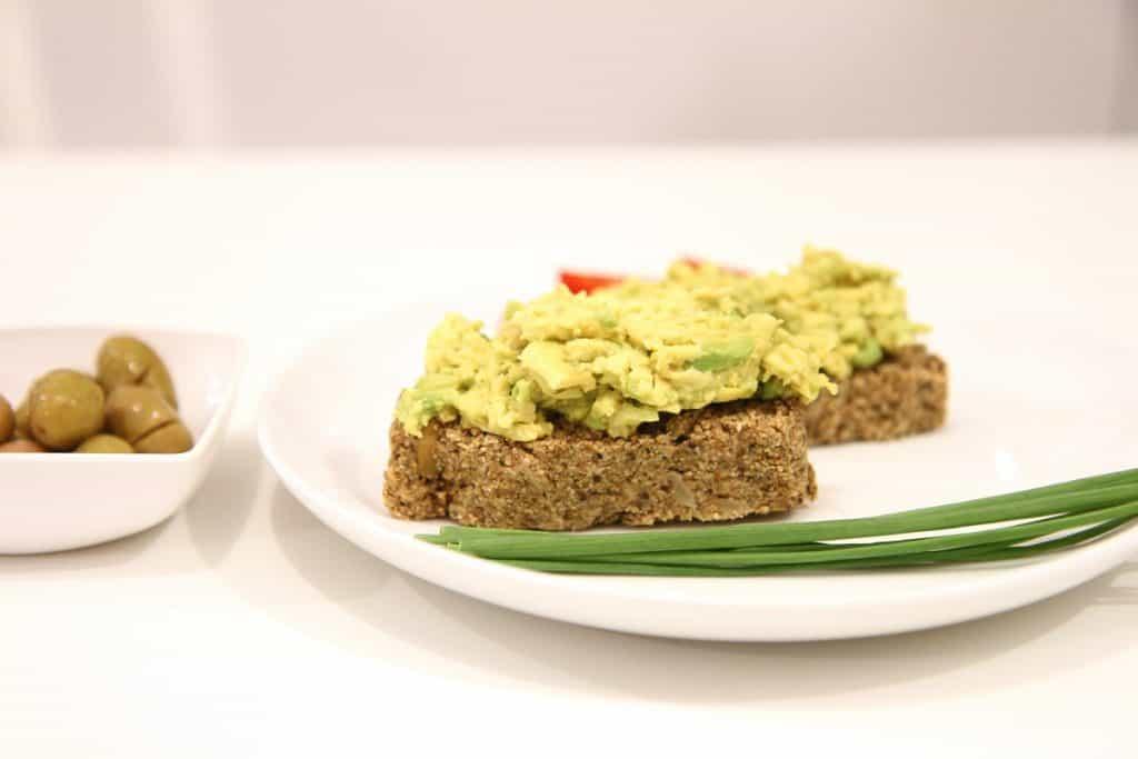 לחם שקדים וכוסמת ללא גלוטן עם ממרח אבוקדו, בצל ירוק וזייתים